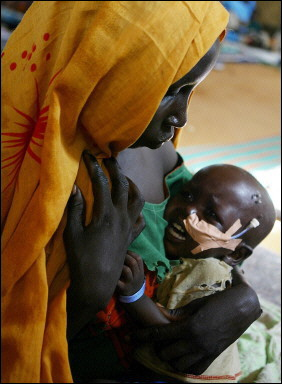 A mother tries to console her child at the Abu Shouk refugee camp near El Fasher in Darfur, Sudan, August 25, 2004  Photo: AFP/Jim Watson