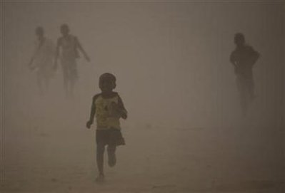 Refugees who fled the conflict in Sudan's western Darfur region run for shelter during a dust storm at Djabal camp near Gos Beida in eastern Chad June 19, 2008.  Photo: Finbarr O'Reilly/Reuters