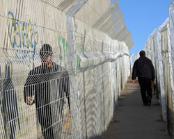 PALESTINIANS WALK IN FENCED LANES BESIDE ISRAELI SECURITY FENCE – Palestinians walk in fenced lanes beside the 30-foot-high Israeli security wall at the entrance to Bethlehem in the West Bank Dec. 19. The wall has created hardship for Palestinians, who must obtain a special permit to cross the Israeli-controlled check point into Jerusalem. Israel maintains that the wall is needed to ensure its security. (CNS)